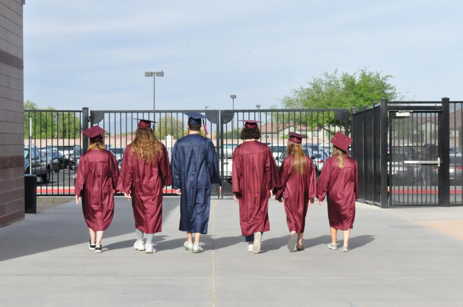 Seniors: Gavin Brennan, Anna Meyers, Nadine Loureiro, Ashlyn Minor, and Makayla Premo wearing their caps and gowns while walking towards off-campus. After their four years of abnormal high school they are ready to graduate and start their new lives.