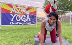 Junior Emma James doing yoga with a goat on her back. AZ goat yoga is one of the many different activities in Arizona to enjoy.