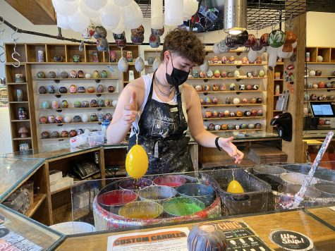 Candle artist Jules dipping candles into vats of colored wax at Sedona Candle Magic. She makes an average of 20-25 candles each day.