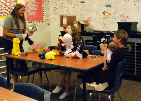 """Juniors Lili Stutz, Savannah Nelson, and Shaye Vannorman (left to right) play with toys in Childhood Education. Students completed """"play labs,"""" in which they evaluated the developmental domains and advantages to the toys."""