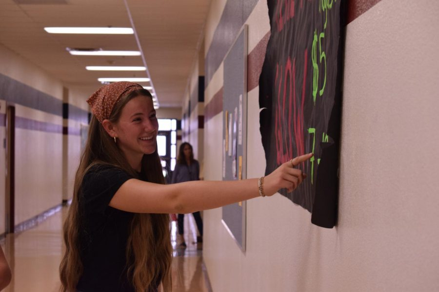 Junior Nicole Baird pointing the Glow Dance poster, telling her friends to come. The dance had a good turnout and danced to trendy and upbeat music to kick off the year.